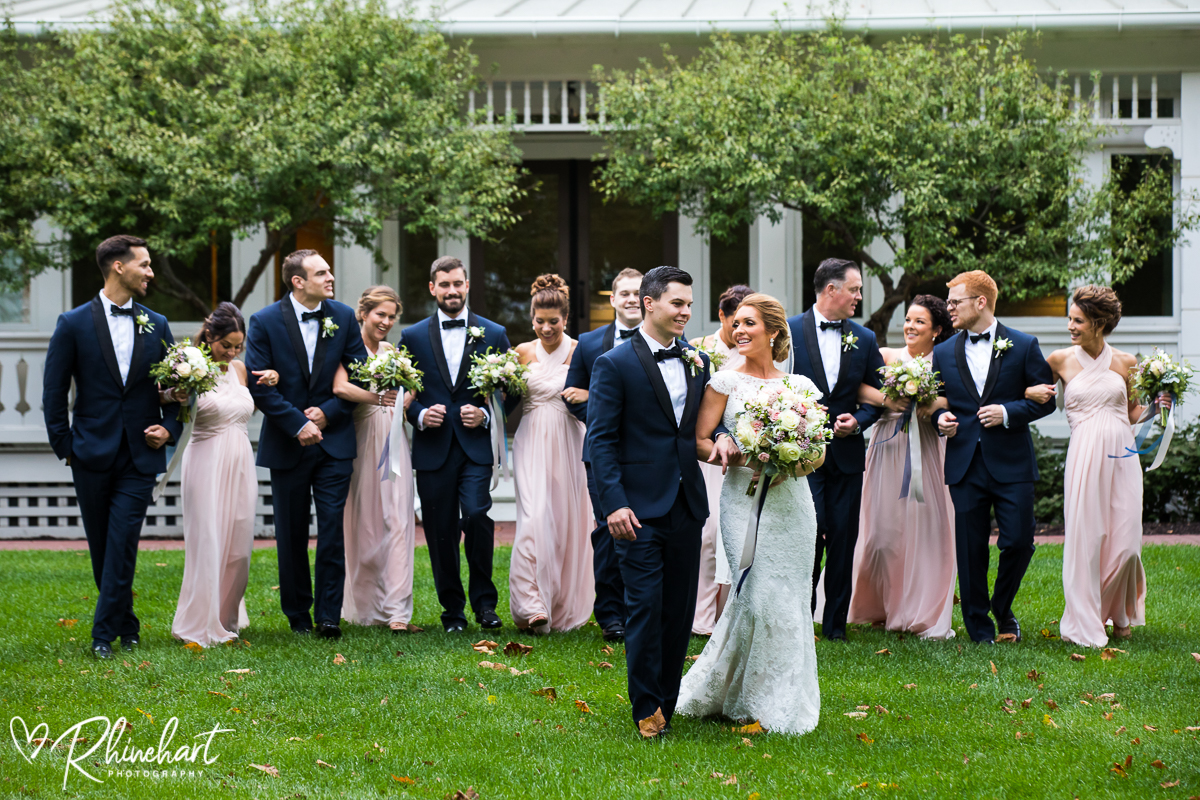 wedding bridal party walks in front of the omni bedford springs resort and hotel photographed by one of the best wedding photographers in pennsylvania