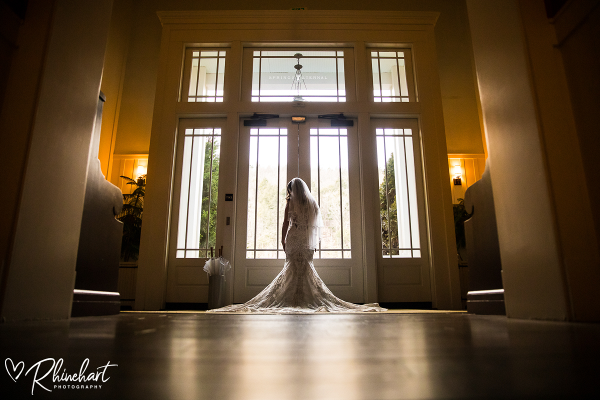 bride stands in front of large window overlooking the spa lawn at the omni bedford springs hotel and resort