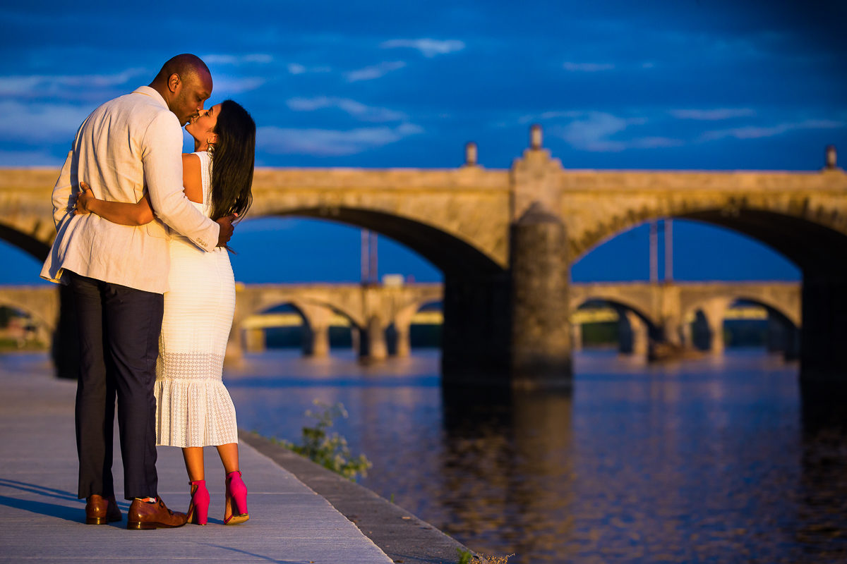 cute couple kisses along front street in Harrisburg as part of their vibrant engagement session