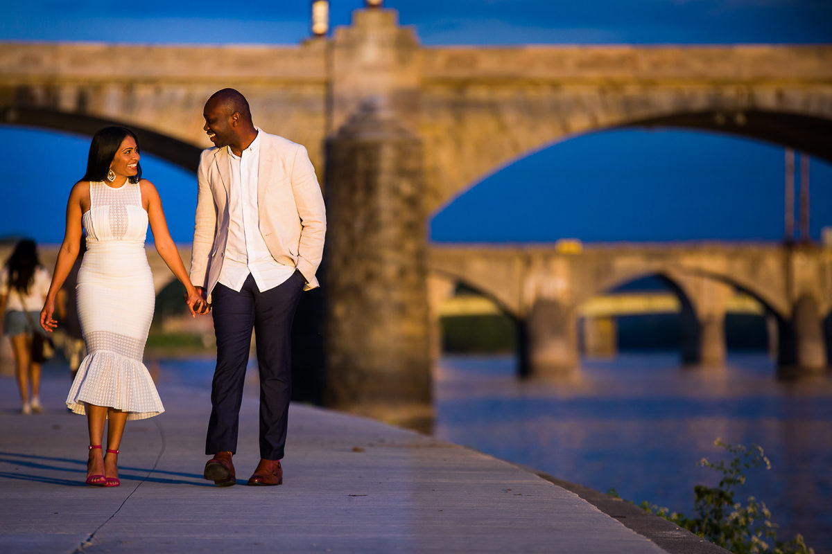 Harrisburg Engagement Photographer Captures couple walking along the Susquehanna with bridges in the background