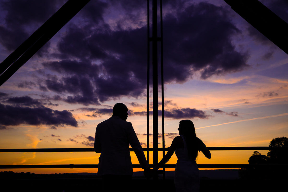 silhouetted couple holds hands on the walnut street bridge for their Harrisburg engagement session