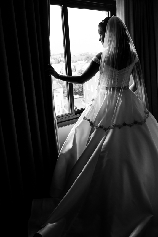 black and white image of bride looking out her window of the darcy hotel