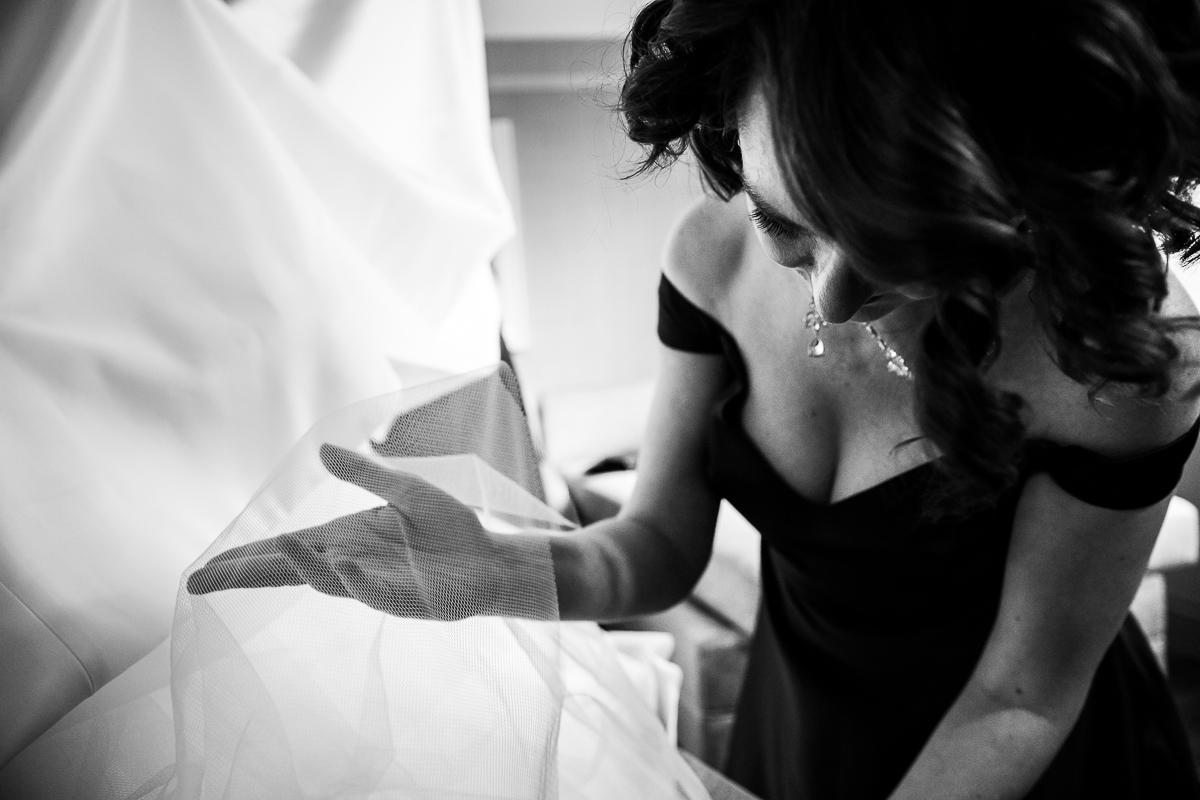 a bridesmaid prepares the bride's elegant wedding gown