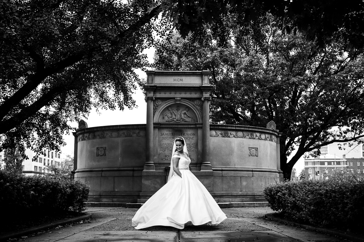 this bride is ready for her first look wearing a wedding gown with pockets in black and white photograph in dc park just outside of the darcy hotel