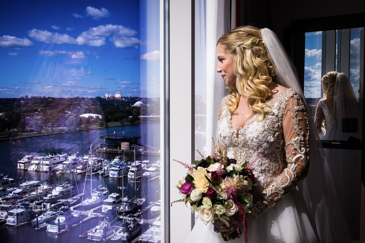 Bride looks out window of the Canopy by HIlton Hotel and overlooks DC wharf a modern chic new wedding venue