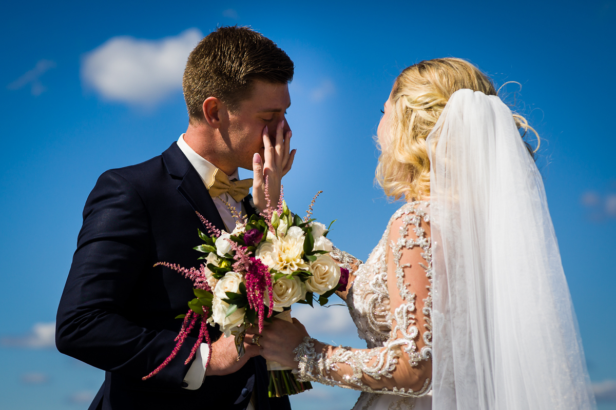 bride wipes a tear from her grooms face during a Washington dc first look