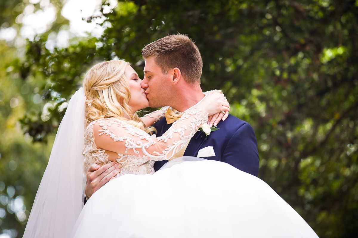 wedding day kiss in meridian hill park groom lifts bride in this classic dc wedding moment