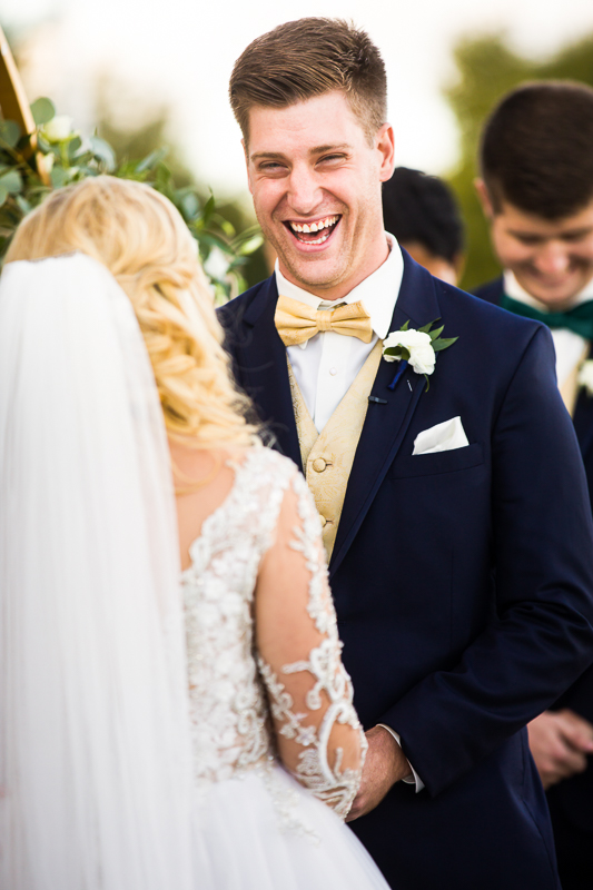 groom laughs and smiles during wedding ceremony in arlington virginia