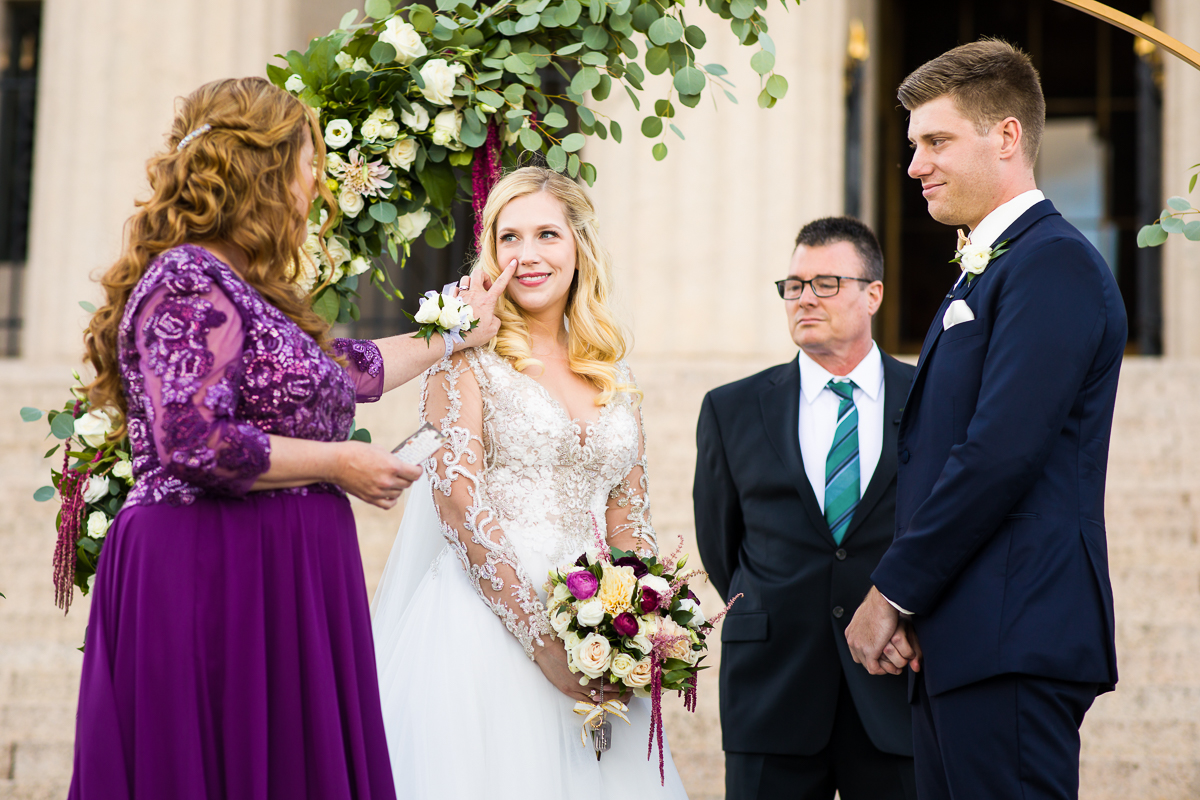 emotional moments captured in Alexandria Virginia at George Washington masonic memorial on the front steps during a wedding ceremony