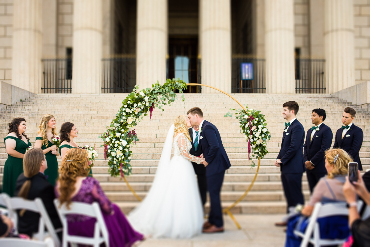 wedding ceremony kiss in floral golden ring in front of the George Washington masonic memorial in Alexandria Virginia