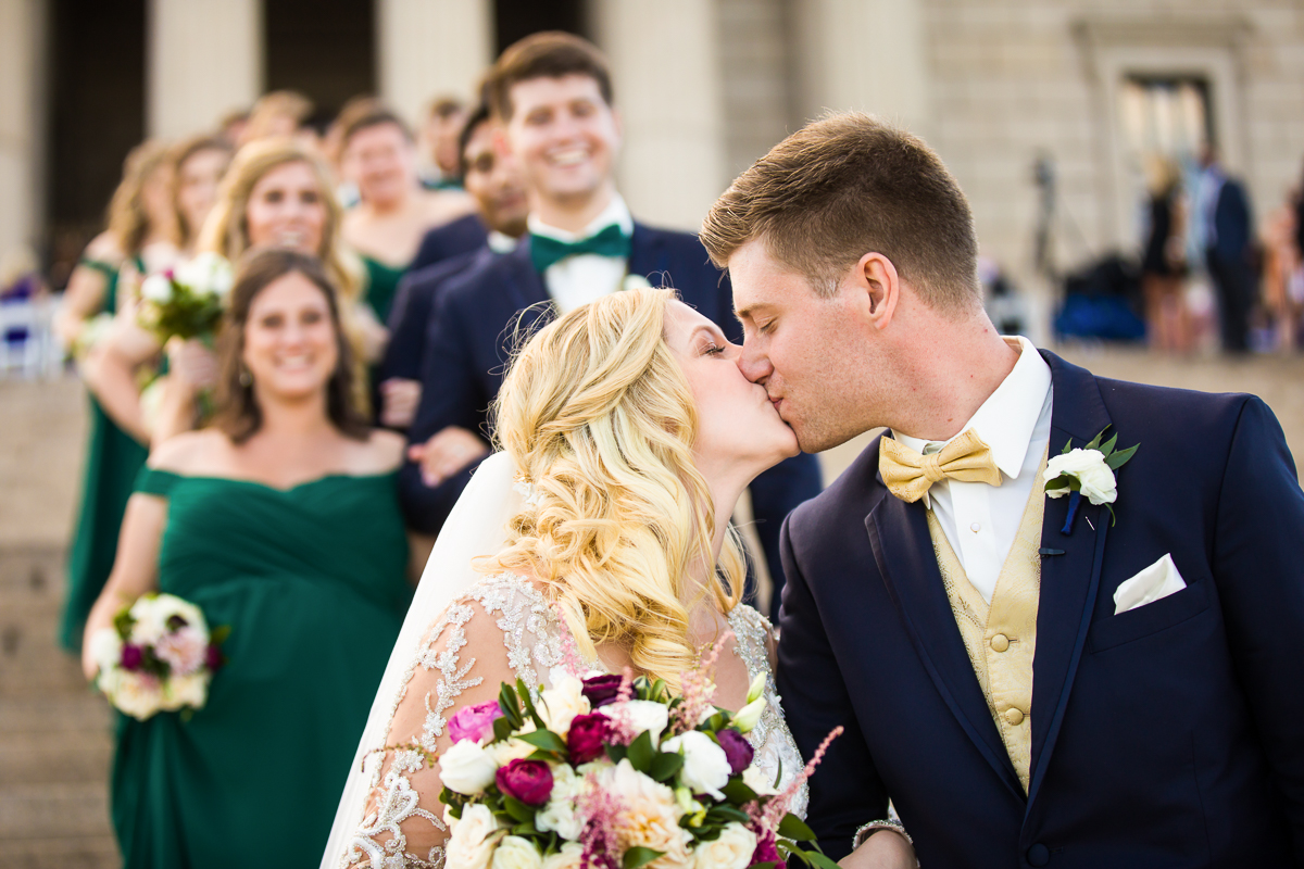 couple kisses with bridal party on steps of GW Masonic Memorial in Alexandria Virginia