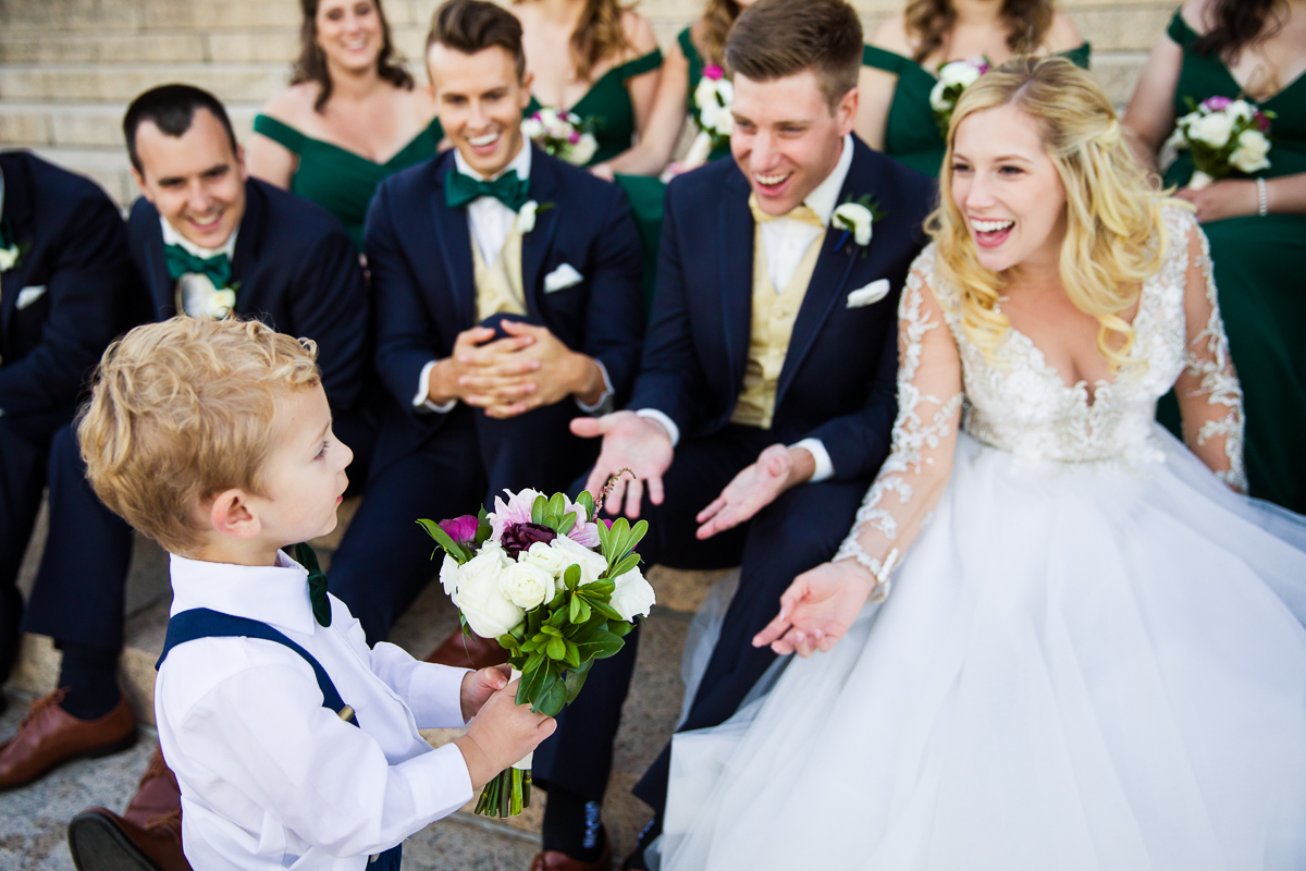 ring bearer gives bride bouquet wearing navy suspenders and bow tie in Arlington Virginia