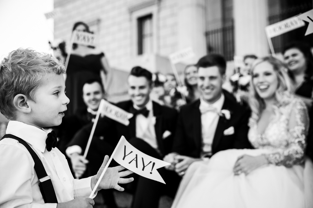 yay banners and signs are held by child caught by classic black and white wedding photographer in Washington dc