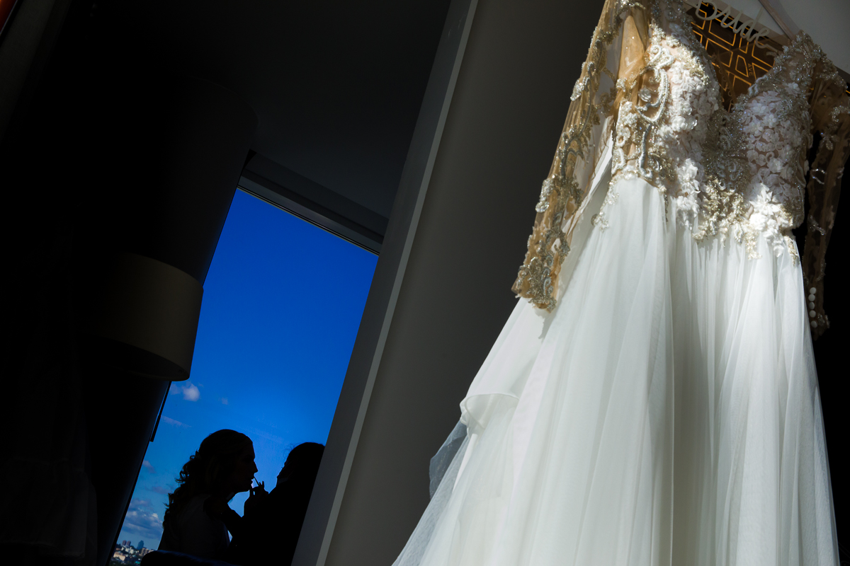 creative wedding photo featuring both the brides preparations and her wedding dress