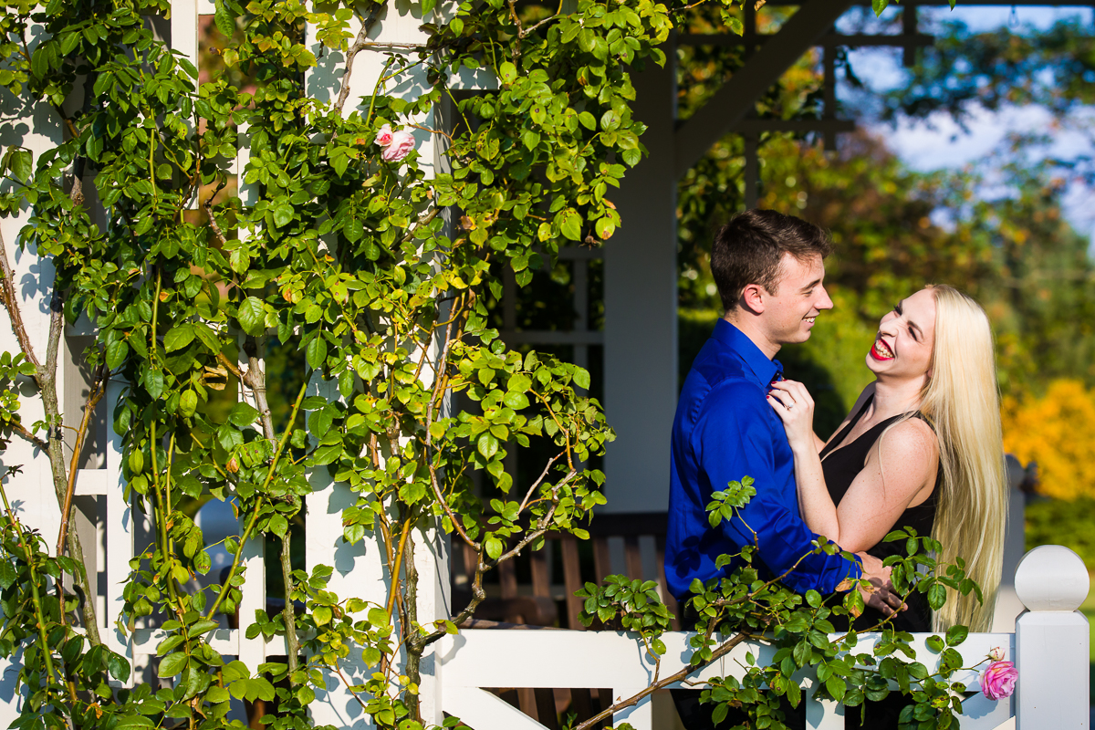 a laughing couple in hershey gardens for their wedding engagement session