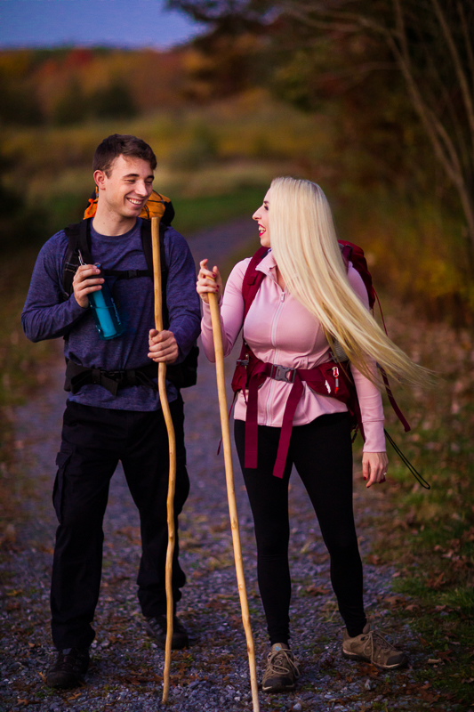Pennsylvania hiking engagement session with a couple wearing backpacks and carrying walking sticks on a trail smiling at each other