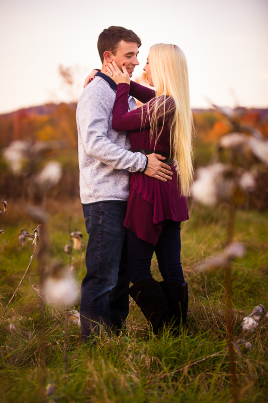 engaged couple in fall toned attire stands in a field with a pennsylvania mountain in the distance