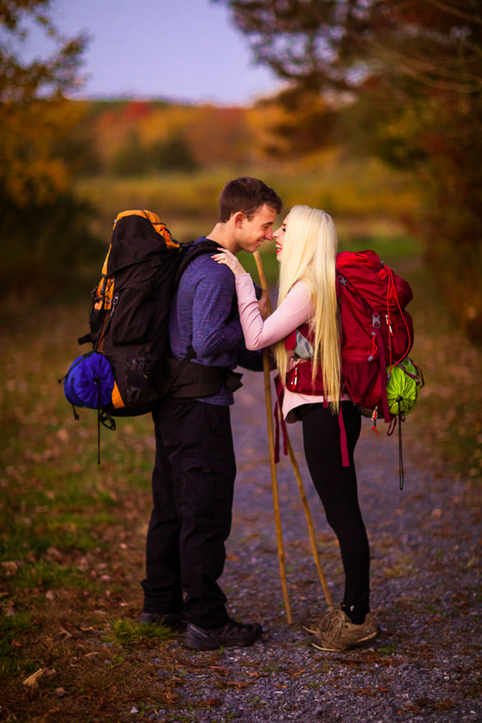 cute couple backpacking through pennsylvania with hiking sticks for their engagement photos