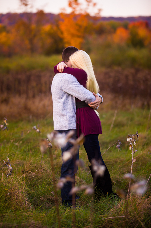 a engaged couple hugging in an open field with pennsylvania mountains in the distance