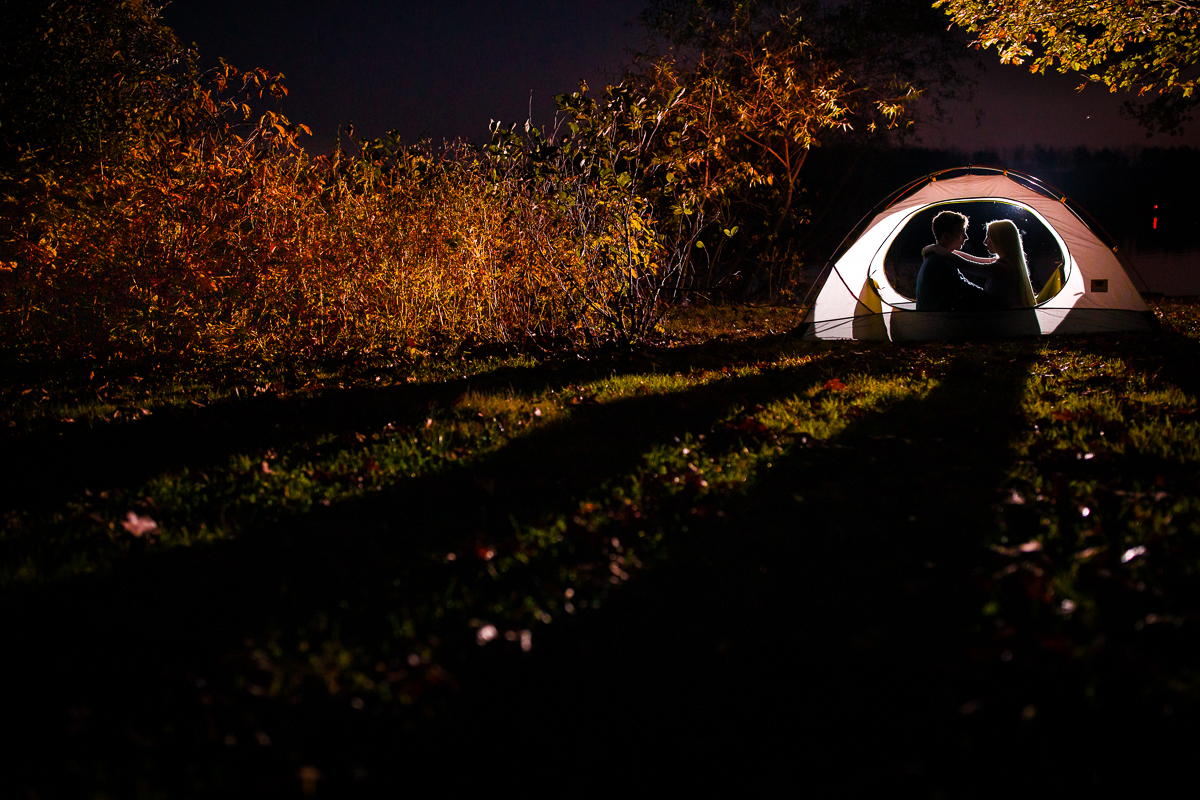 An illuminated tent in Memorial Lake State Park near lvc in autumn with an engaged couple inside