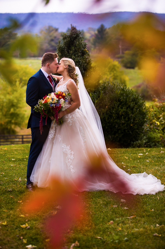 Silverbrook Farm wedding in Autumn with colorful leaves mountains and bride and groom kissing