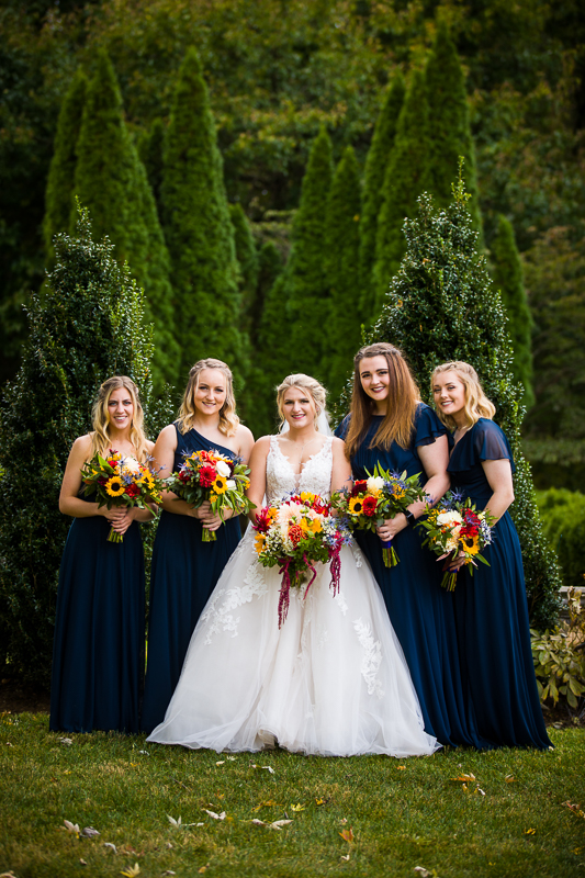 Bridemaids in navy gowns gather in the Silverbrook Farm Wedding garden holding autumn inspired bouquets