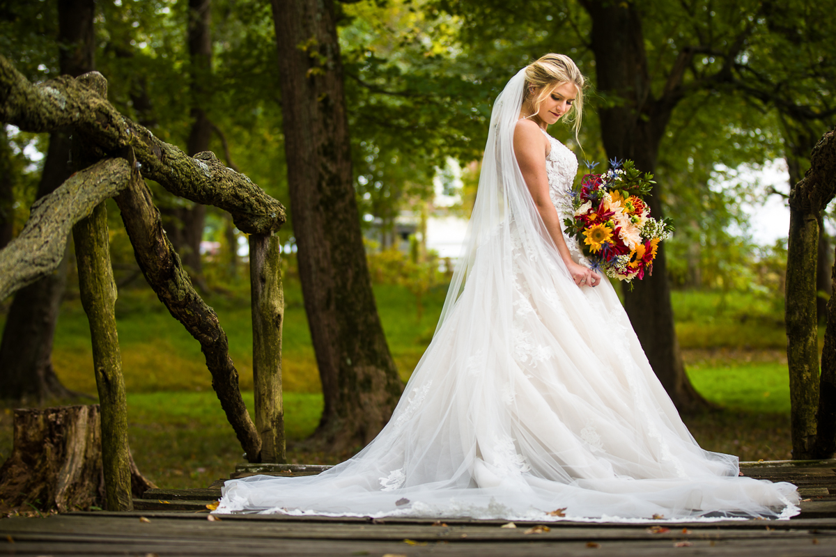 bride stands at bridge holding boquet on silverbrook farm property in Purcellville Virginia