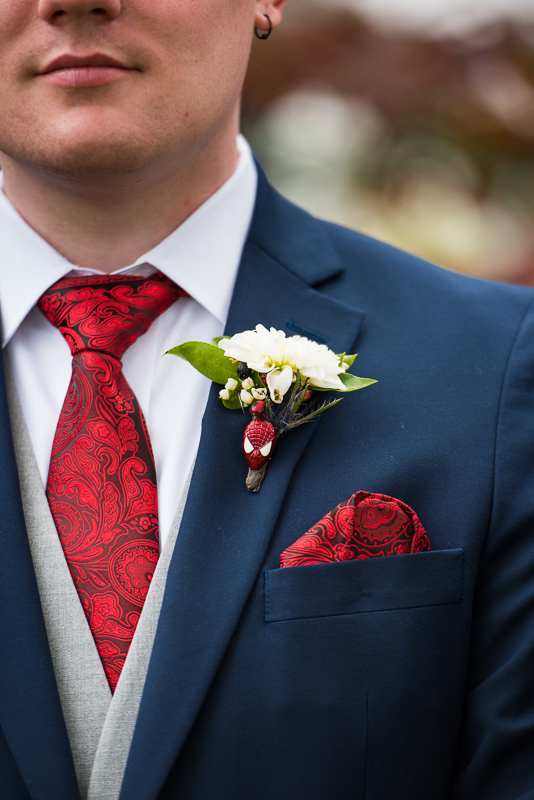 subtle spiderman comic book themed wedding details are shown with a groom wearing a blue suit and Spiderman pin in his boutonniere