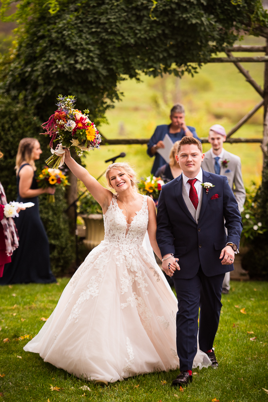 fall silverbrook farm wedding ceremony bride raises hand holding boquet as groom escorts her in a blue suit