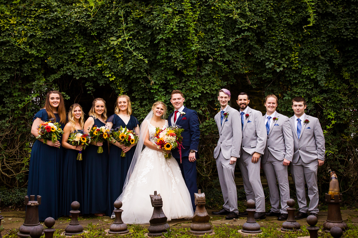 bridal party stands in front of a large wooden chess board at silverbrook farm wedding