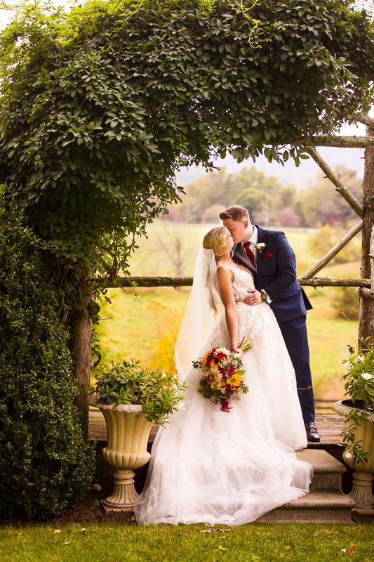 kissing couple under a wedding arch in silverbrook farm