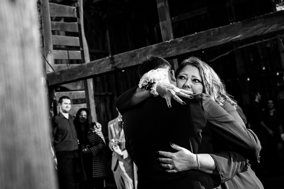 emotional back and white image of a mother hugging her son during the mother-son dance in a Virginia barn
