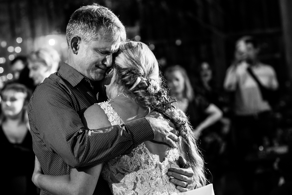 emotional black and white image of a father hugging his daughter the bride