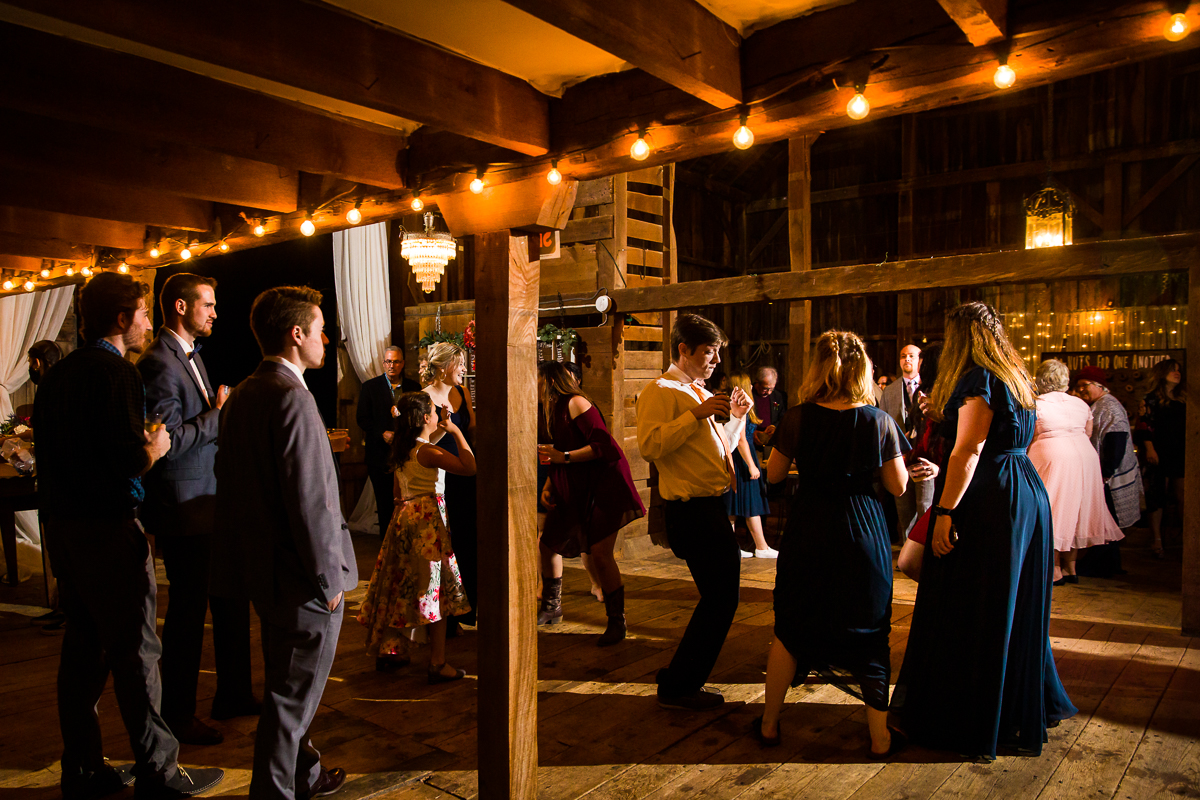 string lights illuminate a barn in virginia for a wedding reception in Purcellville