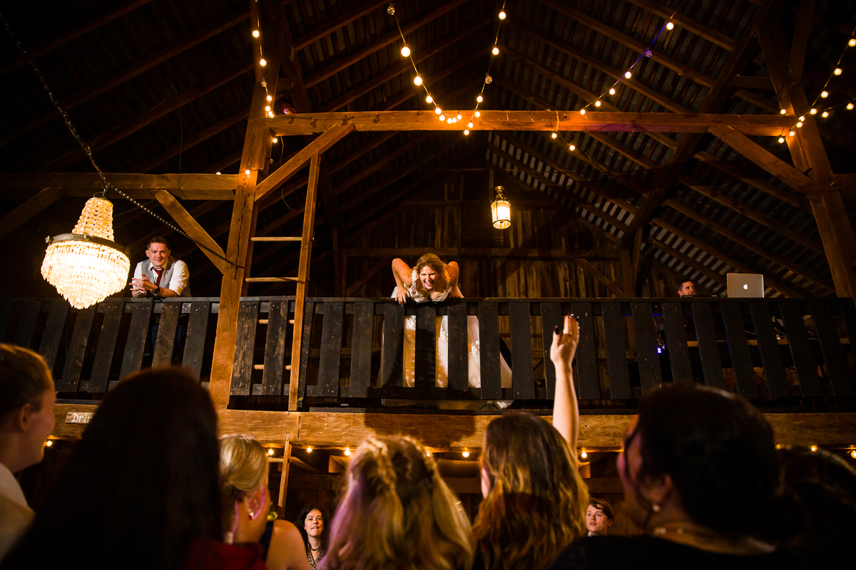 bride laughing during boquet toss in the loft of a barn