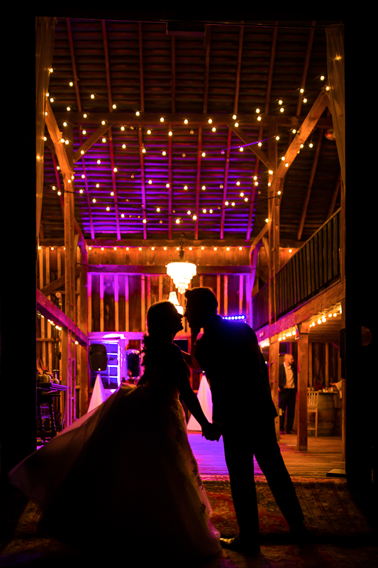 Silverbrook Farm Wedding Reception Barn illuminated with string lights and up lighting in a silhouetted photo