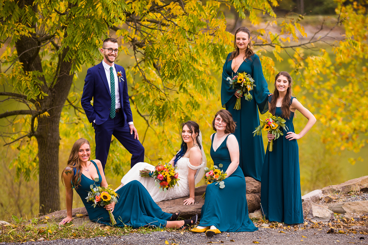 creatively posed bridal party wearing teal posing in front of a yellow lake in autumn