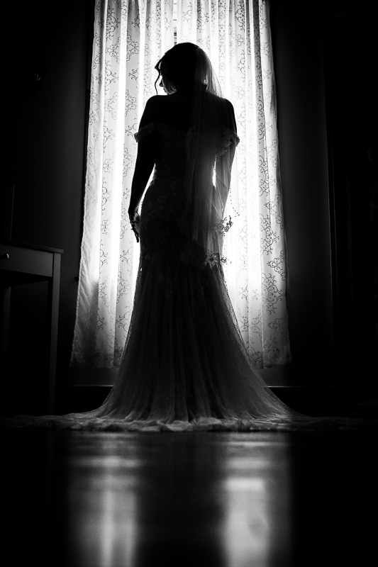 black and white image of bride in window