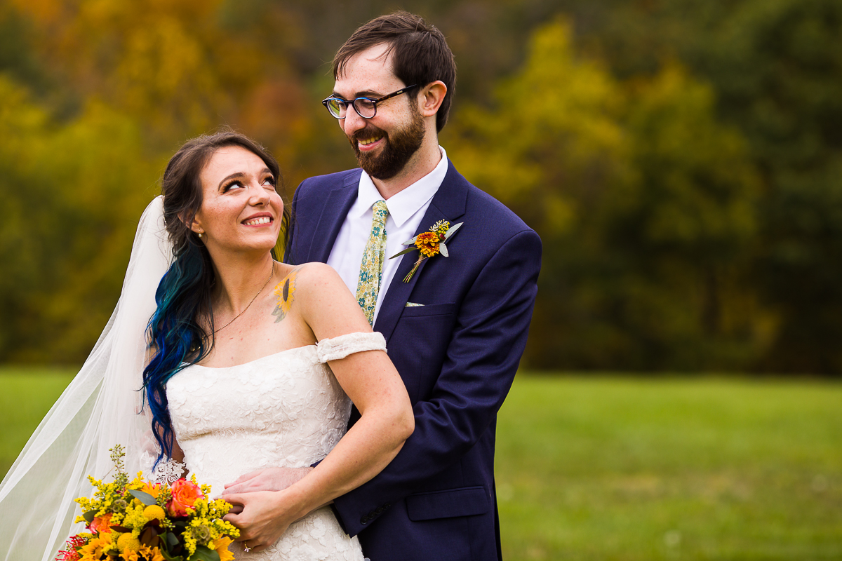 blue haired bride looks up at groom in the fall