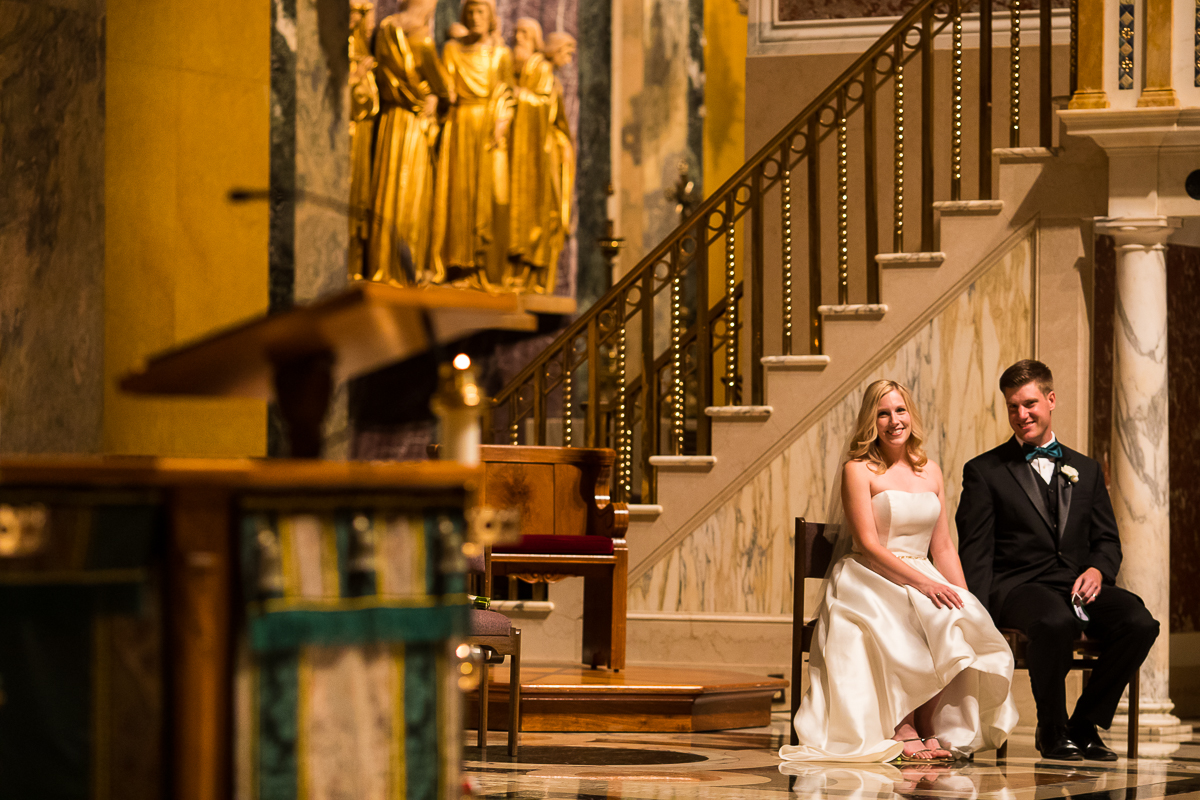 couple sits during their SAINT MATTHEW'S CATHEDRAL WEDDING ceremony