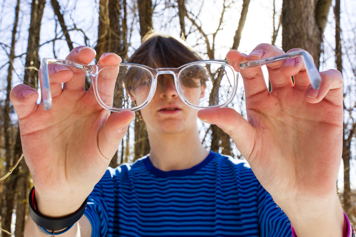 high school senior holds clear glasses with hair in his face and blue t shirt