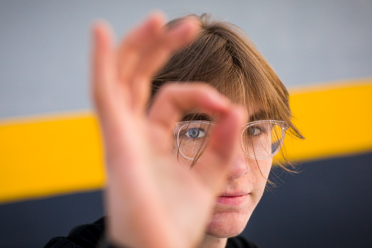 high school senior peeks through his hand with a yellow strip in the background