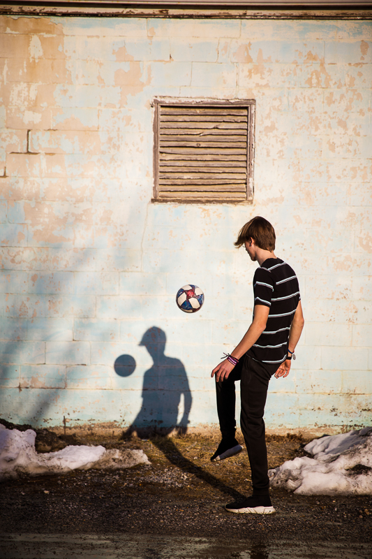 high school senior juggles a soccer ball with a unique shadow