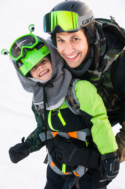 snowboarding dad and child wearing green at blue mountain resort