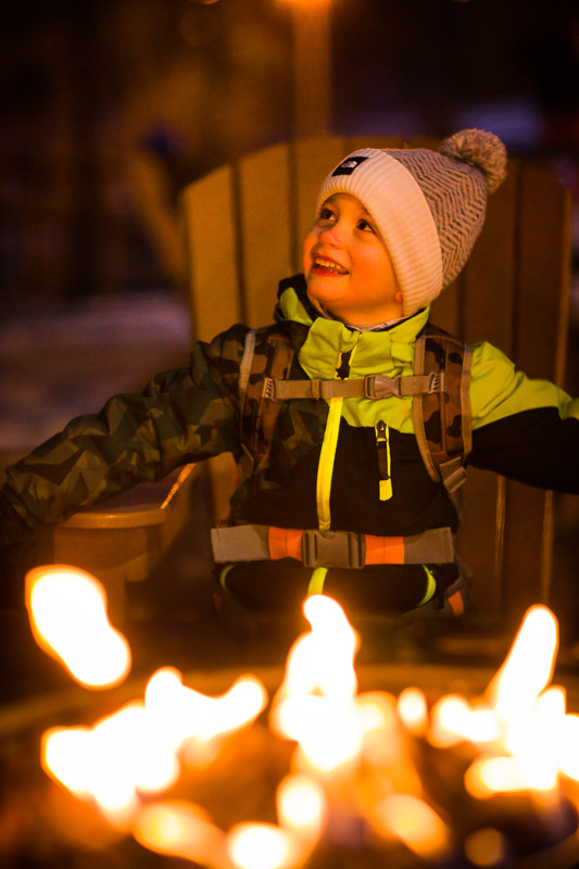 boy smiling campfire after a long day of snowboarding