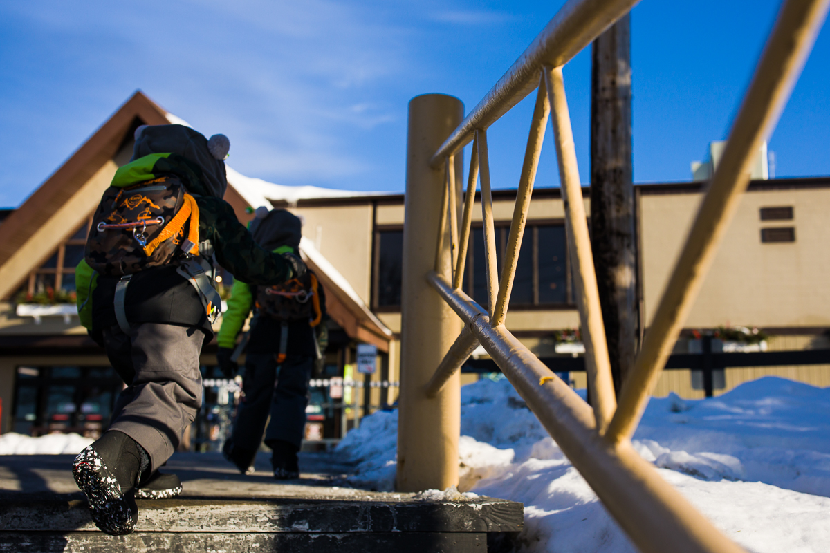 two young boys climbing up the steps of blue mountain resort lodge entrance