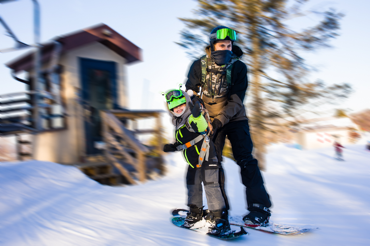 snowboarding child with his father wearing a harness in motion blur at blue mountain resort