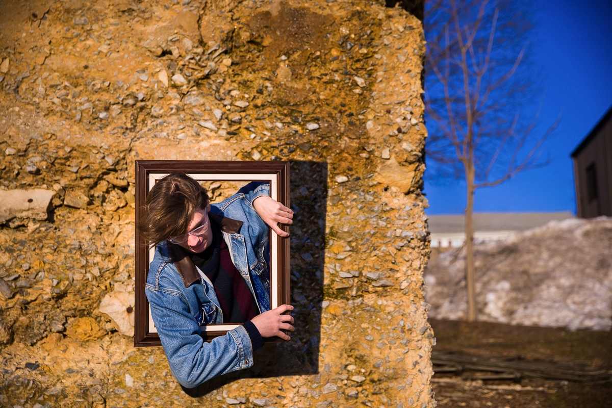 kid climbing through portal as part of his senior portrait photos in pennsylvania with a blue sky and jeans jacket