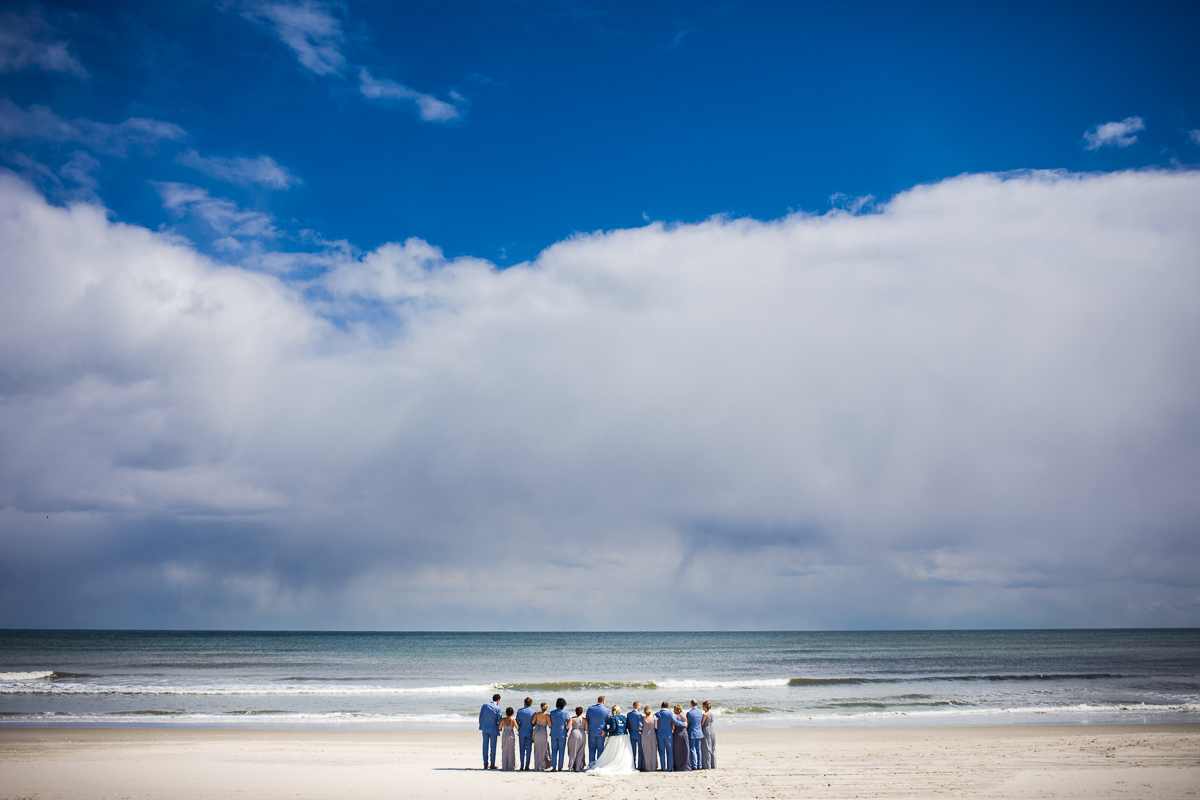 bridal party at the beach overlooking the water and blue sky