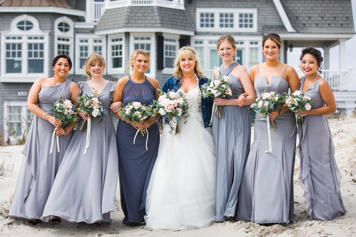 bridesmaids on the beach in stone harbor nj wearing gray dresses and a lace wedding gown and jeans jacket